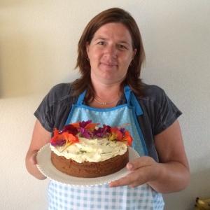 Sandra Poos Reintjes met eigen gebakken taart met bloemen uit de Historische Kruidentuin
